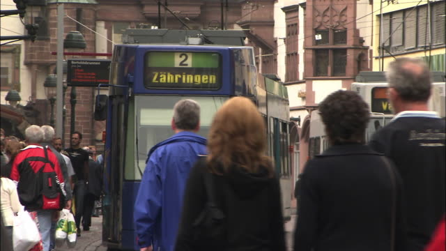 A tram operator moves his vehicle past pedestrians in downtown Freiburg, Germany.