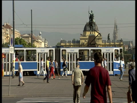 Tram passes by ornate buildings and statues in busy square Zagreb