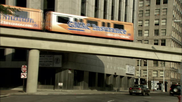 a tram passes over a street in detroit, michigan. available in hd. - michigan点の映像素材/bロール