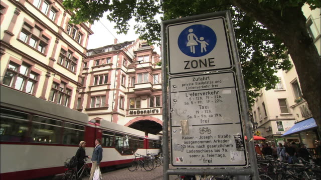 vidéos et rushes de a tram passes storefronts in freiburg, germany. - allemagne