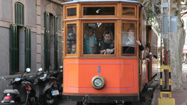 ws tram passing by buildings at puerto soller near soller / mallorca, balearic islands, spain  - バレアレス点の映像素材/bロール