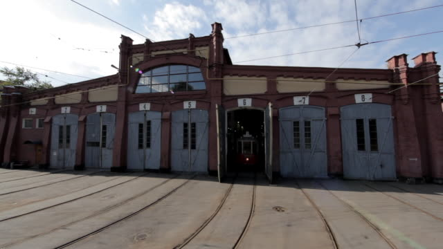 A tram pulls out of a depot building in St Petersburg.