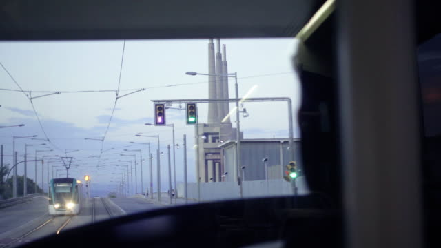 4k | tram railway driver point of view from the cabin wave at another tram driver. industrial zone with big pipes and traffic lights - tram point of view stock videos and b-roll footage