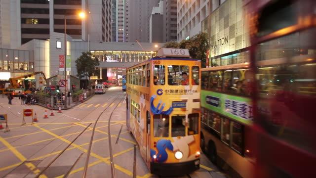 vídeos de stock, filmes e b-roll de ws pov tram riding on busy downtown street at dusk / hong kong, china - ponto de vista de bonde