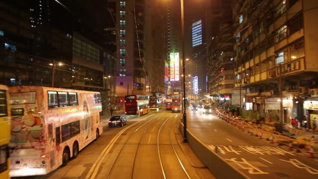 vídeos de stock, filmes e b-roll de ws pov tram riding on downtown street at night / hong kong, china - ponto de vista de bonde