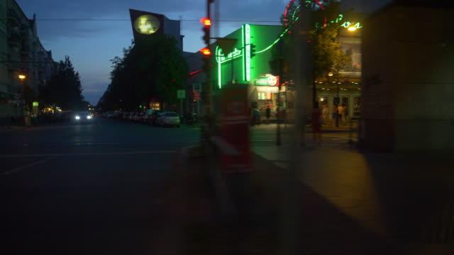 vidéos et rushes de tram side-pov, street lights, buildings with neon lighting, berlin prenzlauer berg in the evening - berlin