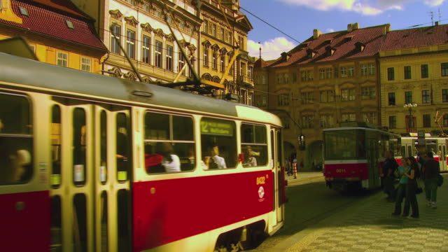 ws tram stop with pedestrians and trams passing by / prague, czech republic - prague stock videos & royalty-free footage
