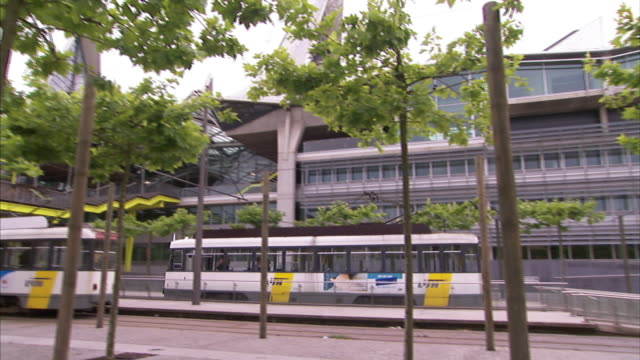 vídeos de stock, filmes e b-roll de a tram travels past trees waving in the wind and a building. - tram