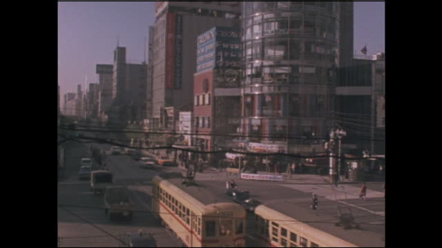 tramcars speed along the ginza 4-chome intersection on the last day of operation for the toden ginza line in tokyo. - showa period stock videos & royalty-free footage