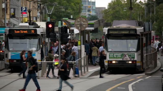 Trams and pedestrians along Flinders Street in Melbourne, Australia.