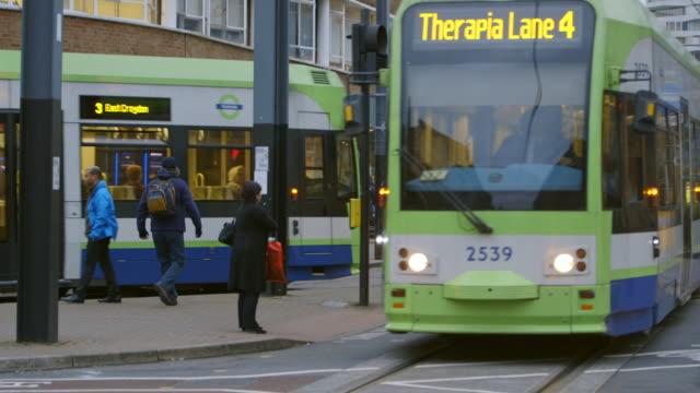 ws trams and pedestrians on croydon high street in croydon / london, england, united kingdom - ロンドン クロイドン点の映像素材/bロール