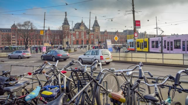 Trams and travellers in front of Amsterdam Central railway station