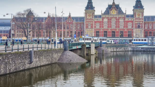 trams and travellers in front of amsterdam central railway station - stazione video stock e b–roll