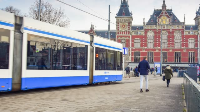 trams and travellers in front of amsterdam central railway station - tram stock videos & royalty-free footage