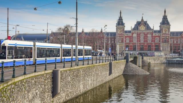 Spårvagnar och resenärer framför Amsterdam centralstation