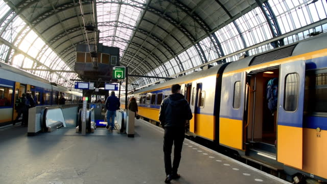 trams and travellers in front of amsterdam central railway station - station stock videos & royalty-free footage