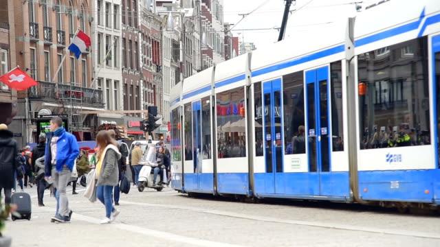 Trams en reizigers tegenover Amsterdam Centraal station