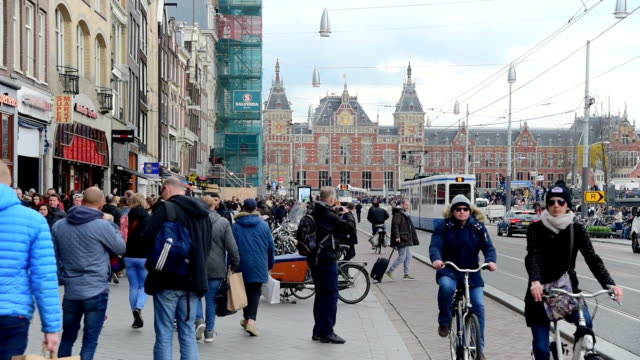trams and travellers in front of amsterdam central railway station - city street stock videos & royalty-free footage