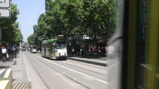 trams are seen on swantson street on december 1, 2016 in melbourne, australia. - 路面軌道点の映像素材/bロール