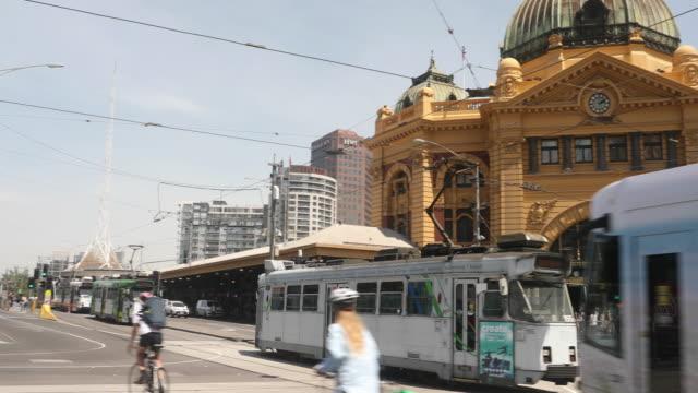 trams are seen passing flinders street station on december 1, 2016 in melbourne, australia. - 路面軌道点の映像素材/bロール