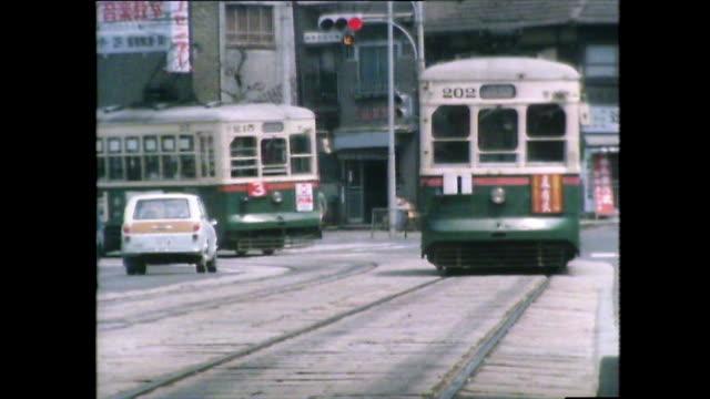 stockvideo's en b-roll-footage met trams moving along busy roads in nagasaki; 1981 - establishing shot