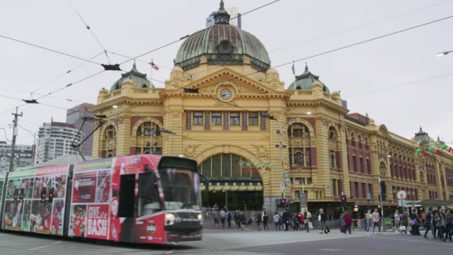 vídeos de stock, filmes e b-roll de ws trams pass in front of flinders street station / melbourne, australia - tram