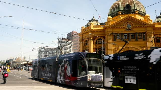 trams seen passing flinders street station. shots of melbourne's iconic transport system taken on december 01, 2016 in melbourne, australia. - 路面軌道点の映像素材/bロール