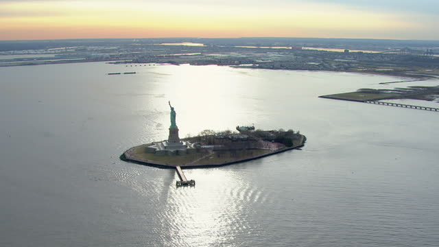 Tranquil aerial view of the famous Statue of Liberty and Liberty Island in New York City at twilight.