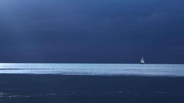 vidéos et rushes de tranquil moody atmospheric film avec un voilier distant à la recherche d'un port sûr avant la tempête - au loin