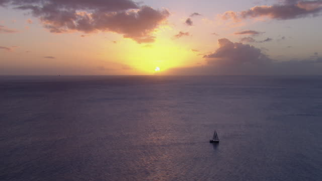 tranquil ocean sunset with sailboat. - sailing stock videos & royalty-free footage