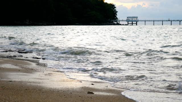 vídeos de stock, filmes e b-roll de mar tranquilo e onda com fundo jetty comprida de madeira no crepúsculo, praia de patong, phuket, tailândia - vista do mar