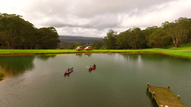 tranquil setting with two kayakers slowly paddling two red canoes along on a lake surrounded by lush green grass jetty in the foreground with two 4wd... - 美しい人点の映像素材/bロール
