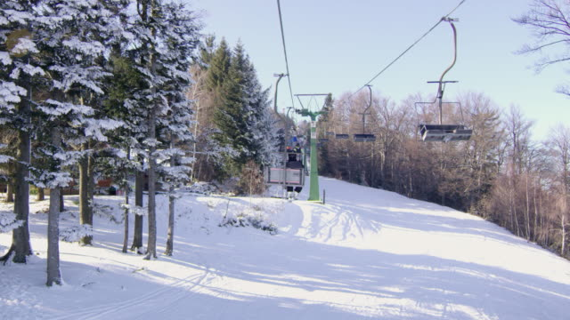 4k tranquil ski lift chairs moving above snowy ski slope, slow motion - inquadratura dalla sciovia video stock e b–roll