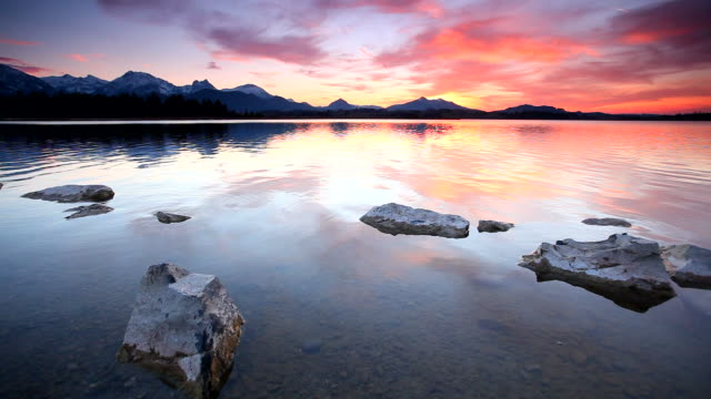 tranquil sunset at lake bannwaldsee in bavaria - germany
