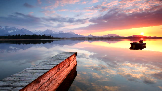 tranquil sunset at lake hopfensee, bavaria with jetty, boat, germany