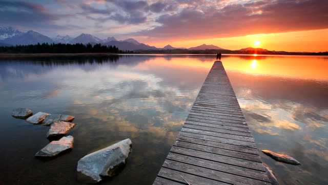 tranquil sunset at lake hopfensee in bavaria with pier- germany