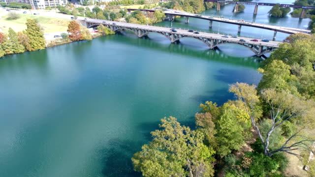 vídeos de stock e filmes b-roll de tranquil town lake pan up to bridges and austin , texas - town