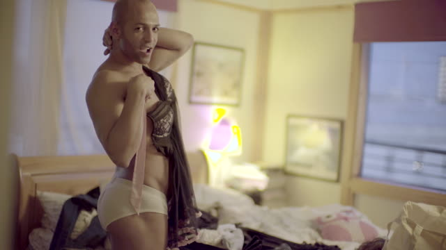 vídeos y material grabado en eventos de stock de a trans gender man in a bedroom. - camisola