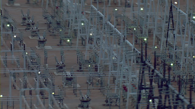 vídeos de stock e filmes b-roll de transformers, utility towers, and power lines cover the grounds of an electrical power substation. - grid