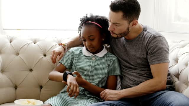 vídeos y material grabado en eventos de stock de transexuales padre con hija con reloj elegante en casa - reloj de pulsera