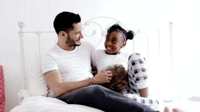 transgender father with his daughter on bed - adoption stock videos and b-roll footage