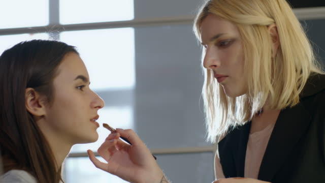 transgender make-up artist applying nude lipstick on young woman - 10 sekunden oder länger stock-videos und b-roll-filmmaterial