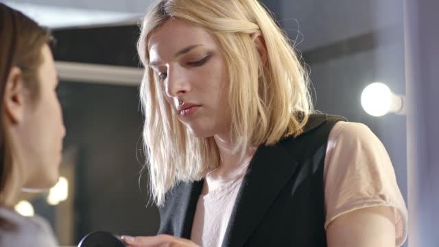 transgender make-up artist applying powder on young woman - genderblend stock-videos und b-roll-filmmaterial