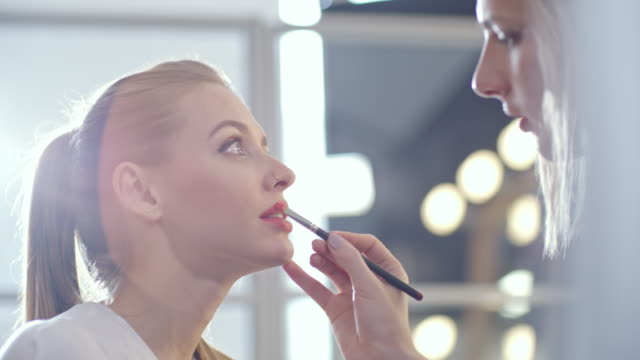 transgender make-up artist preparing young woman for photo shoot - beautician stock videos and b-roll footage