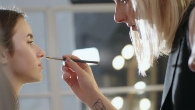 transgender make-up artist working with client - メイクアップアーティスト点の映像素材/bロール