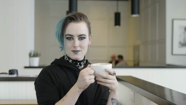 transgender male drinking coffee in cafe. - ermafrodita video stock e b–roll