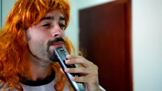 Transgender man shaving his beard