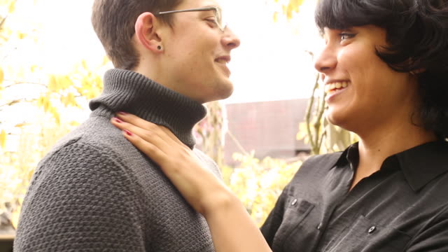 A transgender man with her partner embracing outdoors in a park.