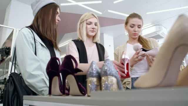 vídeos y material grabado en eventos de stock de transgender person and female friends choosing shoes - genderblend