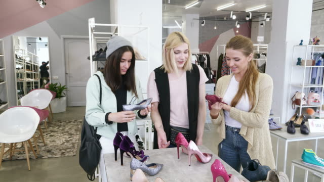 Transgender person and young women discussing stylish shoes in fashion boutique